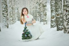 Woman decorates Christmas tree in forest Royalty Free Stock Image