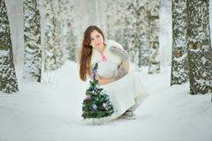 Woman decorates Christmas tree in forest Stock Image