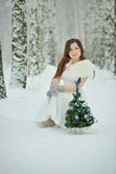 Woman decorates Christmas tree in forest Stock Photos
