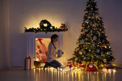 Woman decorates the Christmas tree Garland lights new year holiday gifts white home decor royalty free stock image