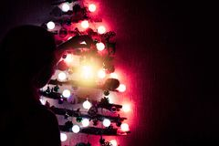 Woman decorates a Christmas tree made of sticks hanging on the wall stock photography