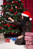 Woman decorates Christmas tree Royalty Free Stock Image