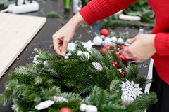 A woman decorates a Christmas wreath. Hands close-up. Master class on making decorative ornaments. Christmas decor with. Manufacturer of Christmas wreath from royalty free stock photography