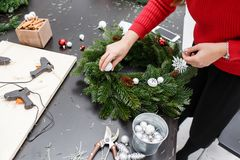 A woman decorates a Christmas wreath. Hands close-up. Master class on making decorative ornaments. Christmas decor with. Manufacturer of Christmas wreath from stock photography