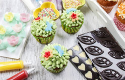 Woman decorates easter cupcakes Stock Photo