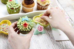 Woman decorates easter cupcakes stock image