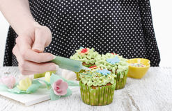 Woman decorates easter cupcakes Stock Photography