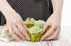 Woman decorates easter cupcakes Stock Images