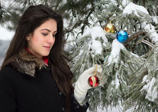 Woman decorates a fir tree. Attractive woman decorates a fir tree with toys in outdoor Royalty Free Stock Photo