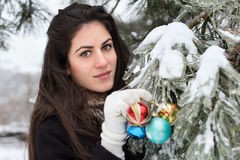 Woman decorates a fir tree. Young beauty woman decorates a fir tree with toys in outdoor Royalty Free Stock Images