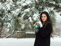 Woman decorates a fir tree. Young woman decorates a fir tree with toys in outdoor Stock Photo