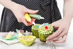Woman decorates green fairy cupcakes Royalty Free Stock Photo