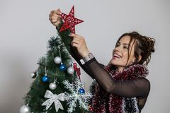 New year tree and woman. Woman decorates a new year tree Royalty Free Stock Image