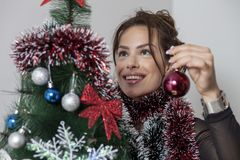 New year tree and woman. Woman decorates a new year tree Stock Images