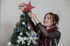 New year tree and woman. Woman decorates a new year tree Royalty Free Stock Photography