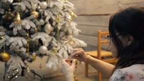 Woman decorates white green Christmas tree with toys inside studio stock video