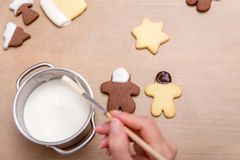 Woman is decorating brown and white cookies with white chocolate royalty free stock image