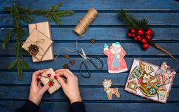 Woman decorating Christmas gifts. Presents wrapping inspirations. Hands, Russian traditional gingerbread cookies, gift boxes, ball