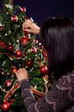 Woman are decorating the Christmas tree Stock Image