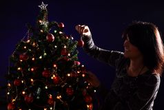 Woman are decorating the Christmas tree Royalty Free Stock Photos