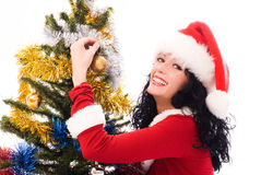 Woman decorating a Christmas tree. Beautiful smiling brunette woman dressed as Santa decorates a Christmas tree Royalty Free Stock Photos