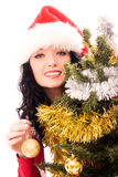 Woman decorating a Christmas tree. Beautiful smiling brunette woman dressed as Santa decorating a Christmas tree Stock Images