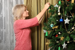 Woman decorating christmas tree Stock Images
