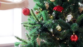 Woman decorating christmas tree with ball stock video