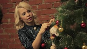 Woman decorating on Christmas tree with Christmas toys. stock video footage