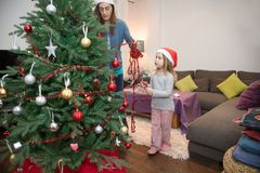 Woman decorating Christmas tree with her little daughter Stock Images