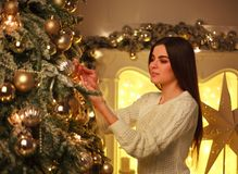 Woman decorating Christmas tree New Year`s toys at home Stock Images