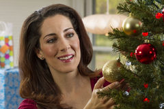 Woman decorating Christmas tree. Royalty Free Stock Image
