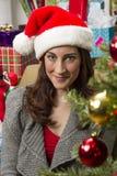 Woman decorating Christmas tree. Stock Photos