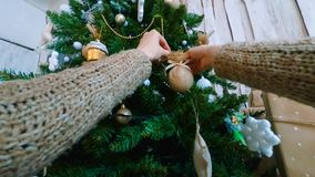 Woman decorating christmas tree with toys. Point of view shot. Holidays, celebration and christmas concept stock images