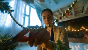 Woman decorating christmas tree with toys. Point of view shot. Holidays, x-mas and christmas concept royalty free stock images