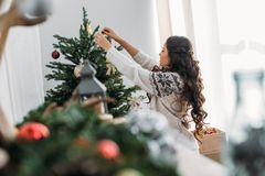 Woman decorating christmas tree. Young beautiful woman decorating christmas tree with hangings Stock Photo