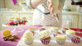 woman decorating cup cakes stock footage - Woman Decorating Cupcakes