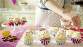 woman decorating cup cakes with sprinkling and berries stock footage