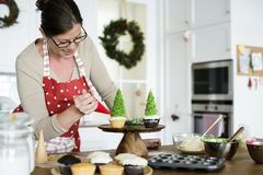 Woman decorating a cupcake hoilday Royalty Free Stock Photo