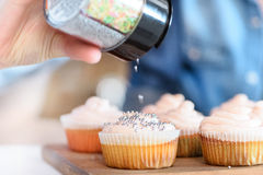 woman decorating cupcakes with confetti stock images