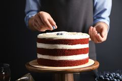 Woman decorating delicious homemade red velvet cake with blueberries. At table royalty free stock images