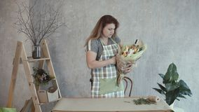 Woman decorating edible arrangement with herbs. Happy redhead woman in apron decorating tasty edible bouquet arrangement with fresh green herbs at workplace stock video footage