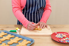 Woman decorating gingerbread men royalty free stock images