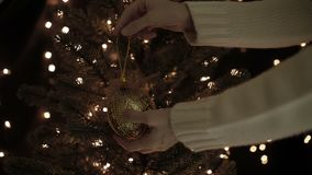 Woman decorating the gold Christmas ball on a Christmas tree with bokeh lights background.  stock footage