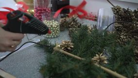 Woman decorating handmade christmas branch with pine cones and shine beads.  stock footage