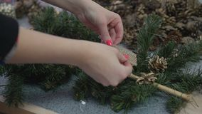 Woman decorating handmade christmas branch with shine beads and pine cones.  stock footage