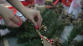 Woman decorating handmade christmas branch with shine beads and pine cones.  stock video