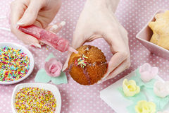 Woman decorating muffins Royalty Free Stock Photos