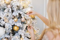 Woman decorating the New Year tree. Christmas tree toy in the form of a stroller. Woman decorating the New Year tree. Christmas tree toy in the form of a Stock Image
