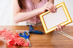 The woman decorating picture frame in scrapbooking concept. Woman decorating picture frame in scrapbooking concept Stock Photo